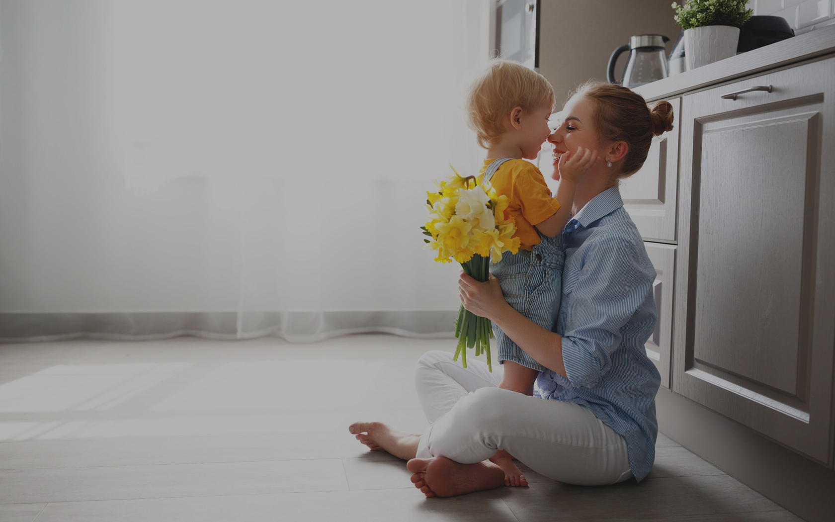 Woman and child embracing sitting on the floor